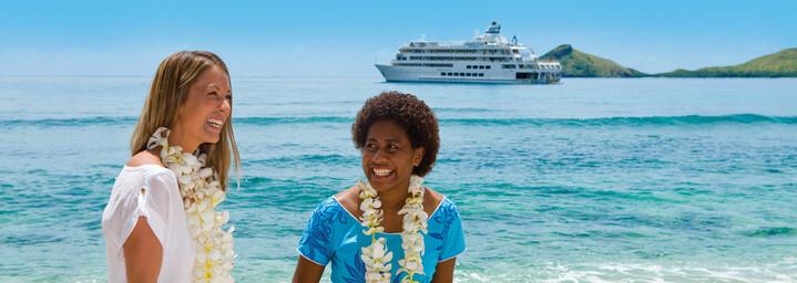 """Frauen am Strand vor Kreuzfahrtschiff """"MV Reef Endeavour"""" Captain Cook Cruises"""