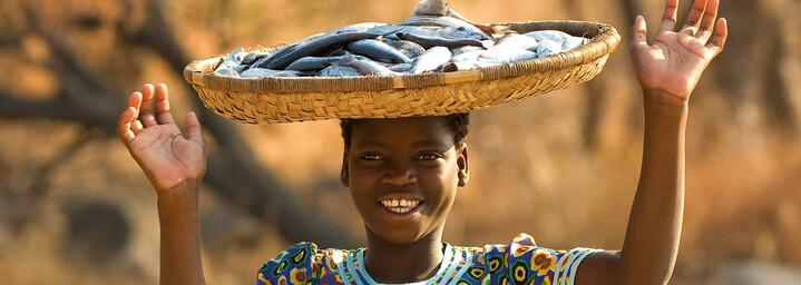 Bewohner eines Dorfes in Malawi mit Fisch