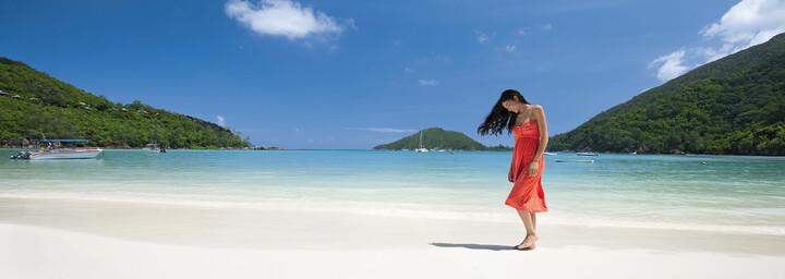 Frau am Sandstrand des Constance Ephélia Seychelles