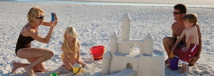 Familie baut Sandburg am Strand von Naples