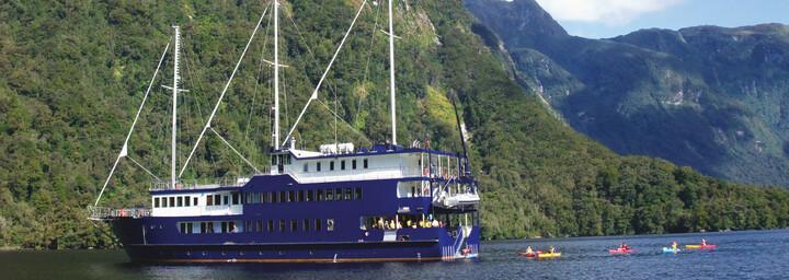 """Außenansicht und Kayakfahrer - Kreuzfahrtschiff """"Fiordland Navigator"""" im Doubtful Sound"""