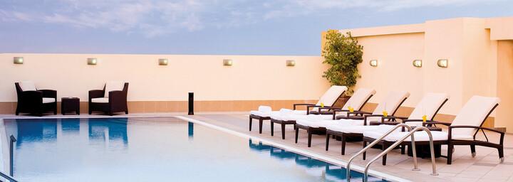 Pool & Sonnenliegen des Avani Deira Dubai Hotel