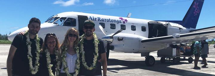 Cook Inseln Reisebericht - Reiseexpertin Jasmin und Mitreisende bei Ankunft mit Blumenkränzen
